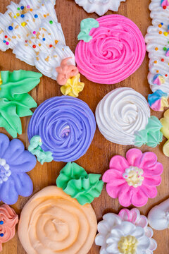 Colorful sweet meringues on a wooden background