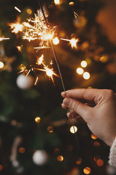 Happy New Year! Hand holding burning sparkler on background of christmas tree lights in festive room. Firework bengal glowing in woman hand. Space for text. Atmospheric moment. Merry christmas
