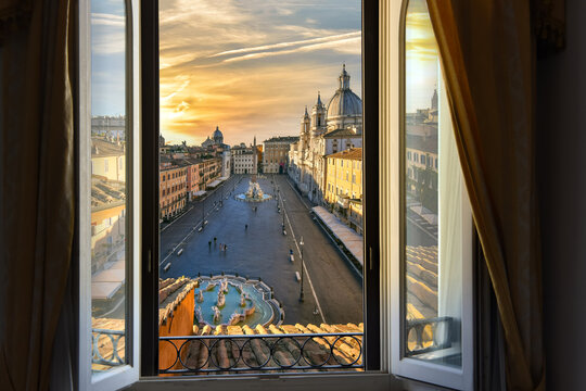 View through an open window of a room overlooking Piazza Navona at sunset in Rome, Italy.