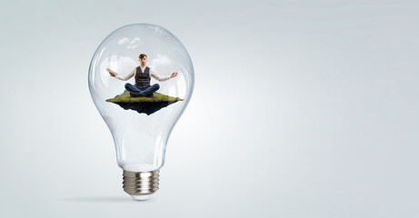 Businessman doing yoga in lotus pose inside light bulb . Mixed media . Mixed media