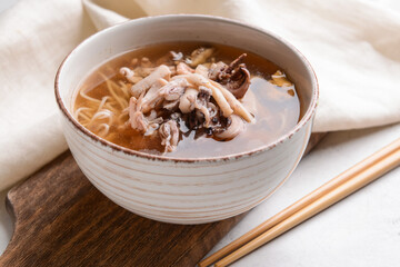 Tasty Chinese soup in bowl on light background, closeup