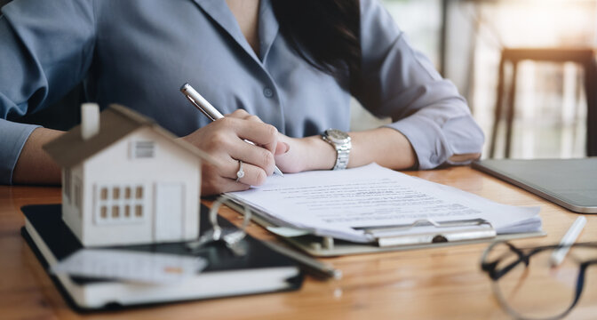 Real estate agent working sign agreement document contract for home loan insurance approving purchases for client with house model and key on wooden desk