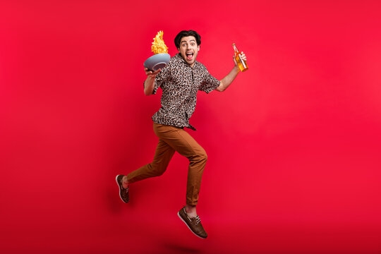 Full size photo of young smiling excited man jumping with beer potato chips carefree isolated on red color background