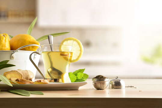 Green tea with ginger and lemon on table in kitchen