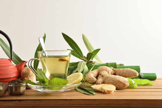 Green tea with ginger and mint on table front isolated