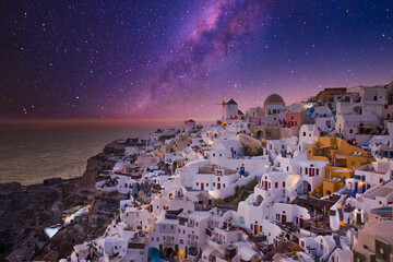 Sunset night view of traditional Greek village Oia on Santorini island in Greece. Iconic travel destination landscape in Greece, famous scenic over traditional white architecture. Luxury vacation