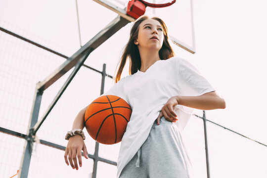 Portrait of young female basketball player. Beautiful teen girl playing basketball. in sportswear playing basketball