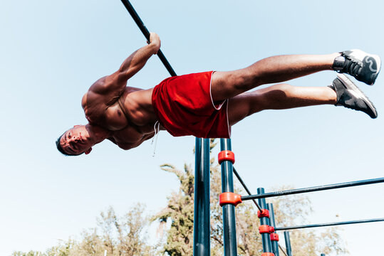 Athlete hanging upside down from a bar in a park.