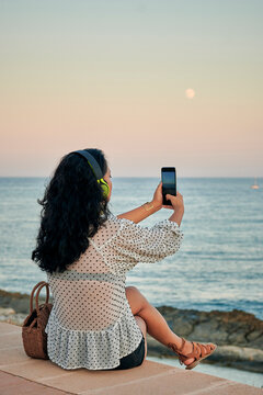 Young Asian woman takes a picture of the sea with her phone