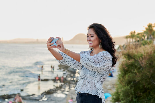 Young Asian woman takes a picture with her phone in a coastal city