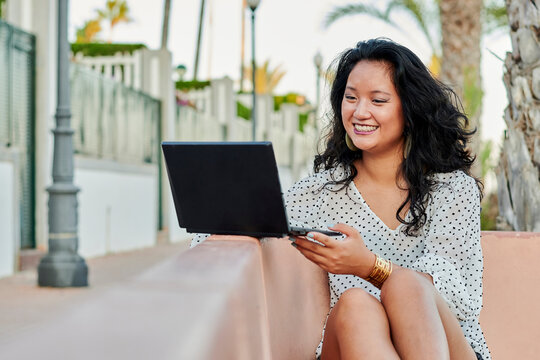 Young Asian woman works with her laptop remotely