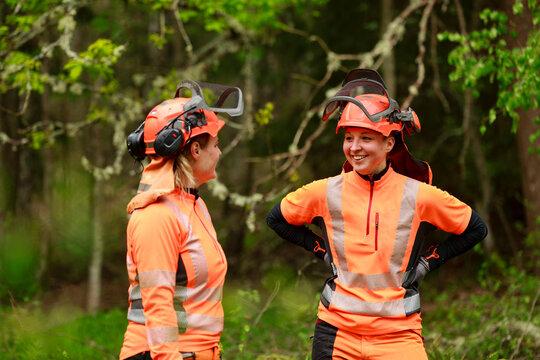 Female lumberjacks smiling in forest