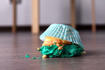 Dropped cupcake with cream on wooden floor at home, closeup. Troubles happen