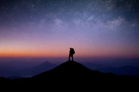 Silhouette of young man traveler with backpack standing and watched the star and milky way alone on top of the mountain. He enjoyed traveling and was successful when he reached the summit.