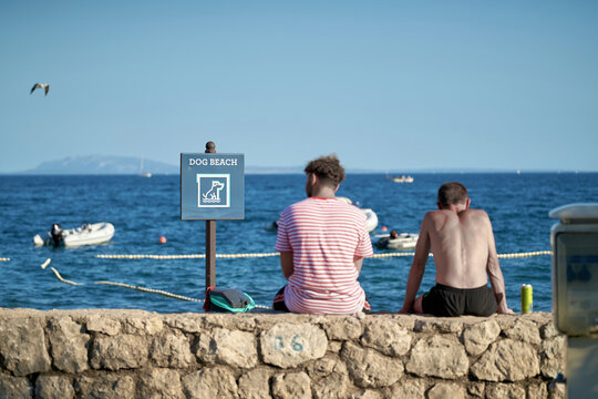 Sign with the inscription dog beach on a campsite in Krk in Croatia. Next to it two vacationers resting on a wall.