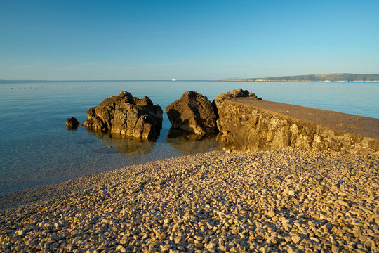 Bathing place with piled up gravel on the actually rocky coast of Krk in Croatia