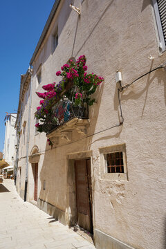 Balcony of a house in the old town of Rab in Croatia with many flowers as decoration