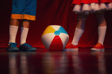 Obraz Closeup view of a girl and a boy dressed and playing wit the ball standing on the stage - fototapety do salonu