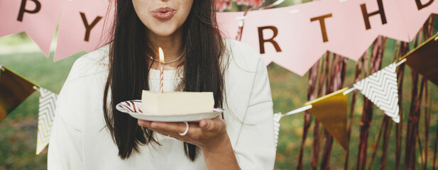 Obraz Stylish happy woman in party hat blowing candle on piece of birthday cake and making a wish on background of pink happy birthday garland in park. Celebrating birthday at picnic party outdoor. - fototapety do salonu