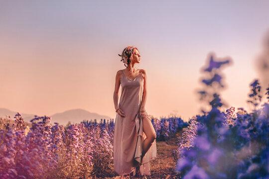 beautiful young stylish woman posing on the field at sunset