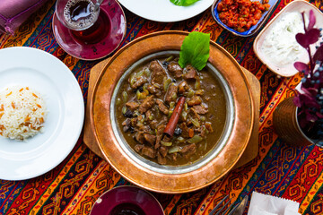 Turkish lamb meat saute mutancana with prunes and rice in traditional ceramic plate