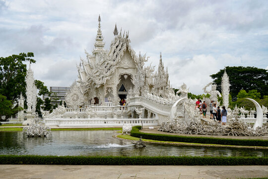 Chiang Rai, THAILAND - July 20, 2021: famous white temple, horizontal photo during the day, snow-white structure, greenery, pond