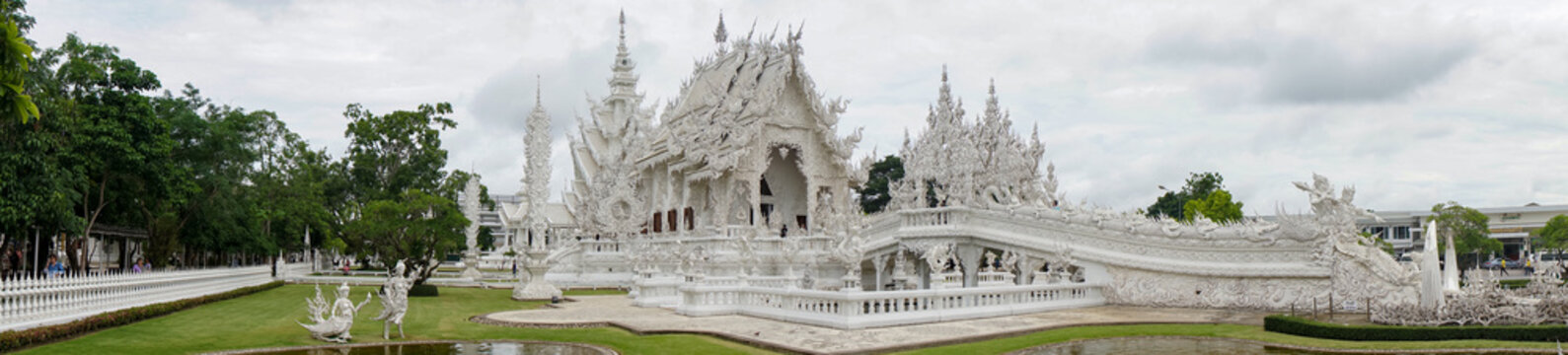 Chiang Rai, THAILAND - July 20, 2021: famous white temple, panoramic photo during the day without people, snow-white structure, greenery, pond