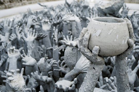 Chiang Rai, THAILAND - July 20, 2021: famous white temple, hands of sinners in hell, sculpture, unusual art object, the palms are holding the pot