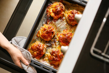 Woman taking baking tray with minced meat boats, mushrooms and cheese out of oven