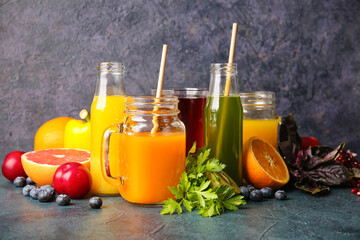 Bottles with healthy juice, fruits and vegetables on dark background