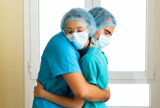 Doctors in uniform hugging in clinic