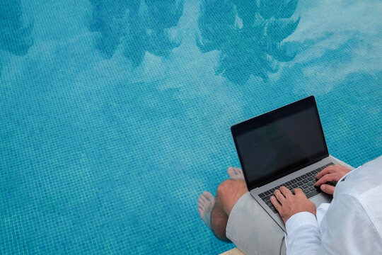 Young man wearing white linen shirt working on laptop by the pool, dipping his feet in a water. Male travel blogger typing on keyboard. Perks of being a freelancer. Close up, copy space, background.