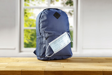 School backpack on wooden table and window in home interior.