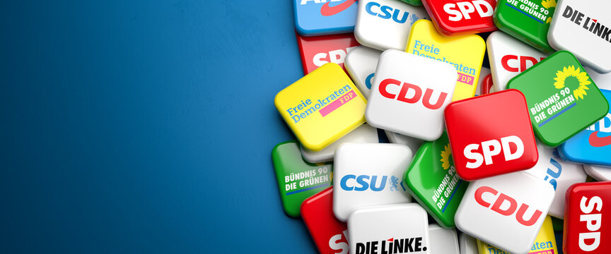 Logos of the biggest German political parties (CDU CSU, SPD, Die Grünen, FDP, Die Linke, AfD) running for the Bundestag election on a heap on a table. Copy space.