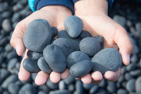 Hands holding small black stones