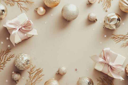 Christmas banner. Beige Xmas background with golden balls, decorative branches, gift boxes. Christmas frame, greeting card template, web banner mockup. Flat lay, top view, copy space