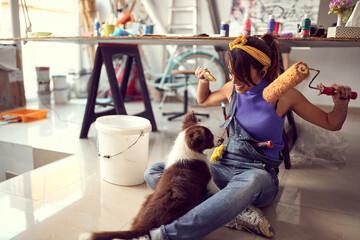 Happy female artist having fun with her dog