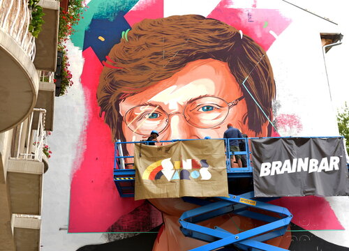 A painter makes finishing touches on a mural showing a portrait of Katalin Kariko, a Hungarian-born scientist and senior vice president at BioNTech in Budapest