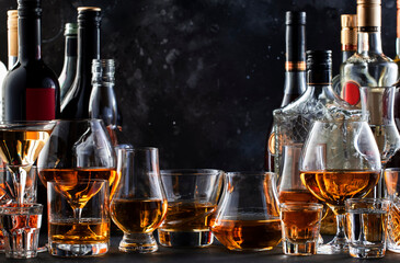 Strong alcohol drinks, hard liquors, spirits and distillates iset in glasses and bottles: cognac, scotch, whiskey and other. Black bar counter background
