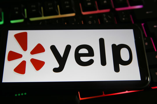 Viersen, Germany - June 9. 2021: Closeup of mobile phone with logo lettering of yelp on computer keyboard