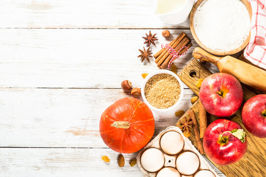 Autumn baking background. Ingredients for baking - flour, sugar, apples and spices. Top view at white wooden table.