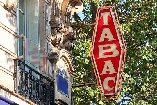 """Vieille enseigne vintage """"Tabac"""" rouge, en français, accrochée à la façade d'un buraliste à Paris – août 2021 (France)"""