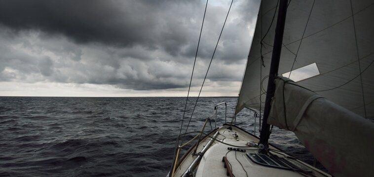 White yacht sailing in an open sea during the storm. View from the deck to the bow. Rough weather, dramatic sky, dark clouds, waves, water splashes. Transportation, travel, sport, leisure activity