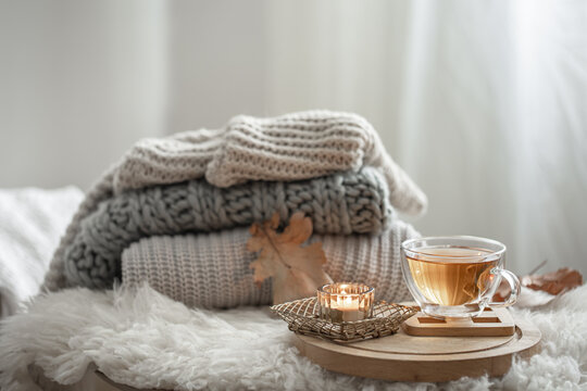 Cozy autumn composition with a stack of knitted sweaters and tea.