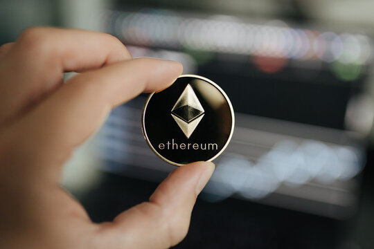 Ethereum cryptocurrency, physical coin close-up held between two fingers