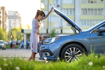 Obraz Helpless woman standing near her car with open bonnet inspecting broken motor. Young female driver having trouble with vehicle. - fototapety do salonu