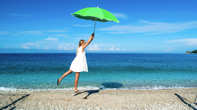 Young girl in a white dress with a green umbrella in her hands is raised by the wind over a pebble beach.