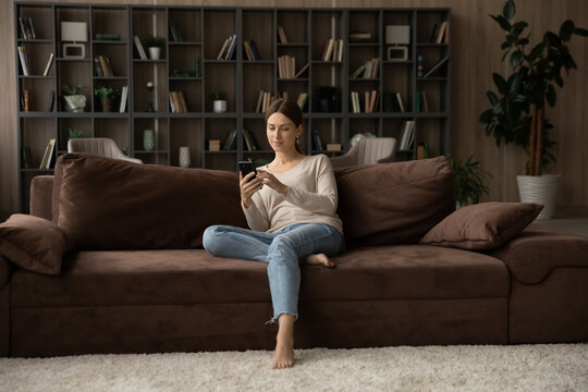 Full length woman holding smartphone, sitting on couch at home, attractive young female looking at phone screen, chatting in social networks with friends, shopping, browsing mobile device apps