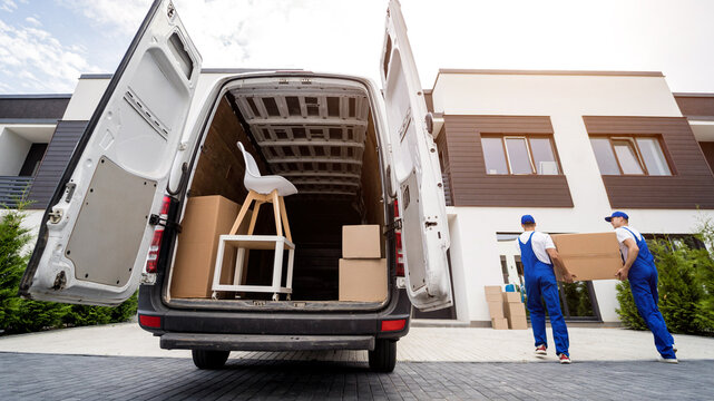 Two removal company workers unloading boxes and furniture from minibus