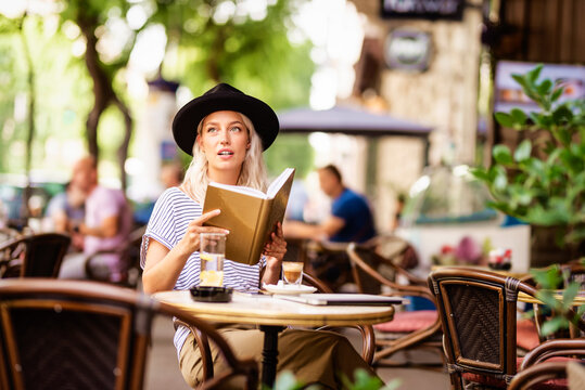 Stylish young woman reading a book while sitting in the outdoor cafe terrace